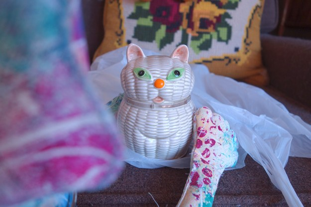 Whimsical cat doll poses with ceramic cat piggy bank.