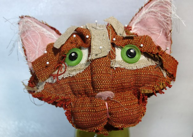 The head of an orange soft-sculptured cat doll with pins holding fabric in place.