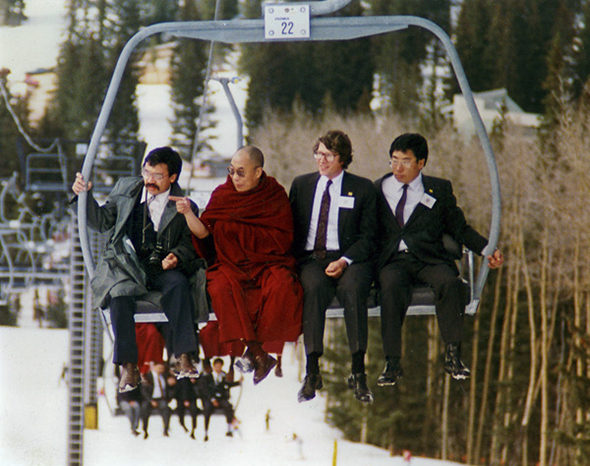 The Dalai Lama is riding a ski lift with a group of men in suits.
