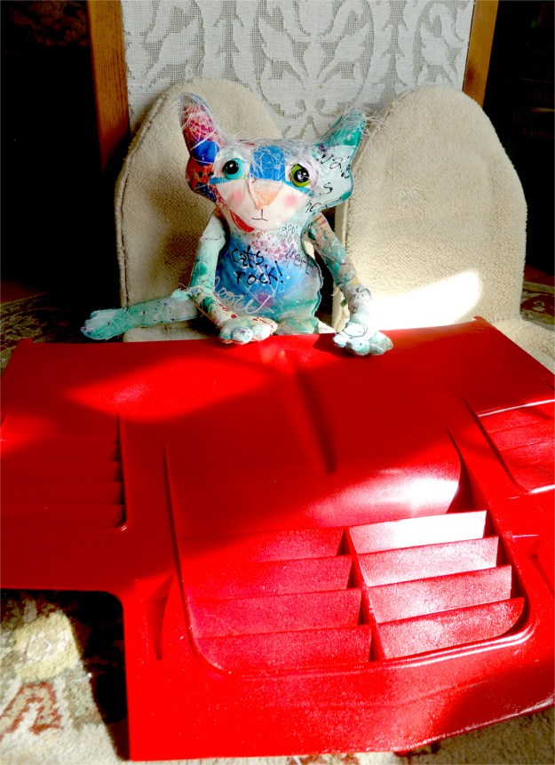 The Chairman cat doll is sitting on a seat taken out of his car, with a bright red car hood on the floor in front of him. The hood looks great!