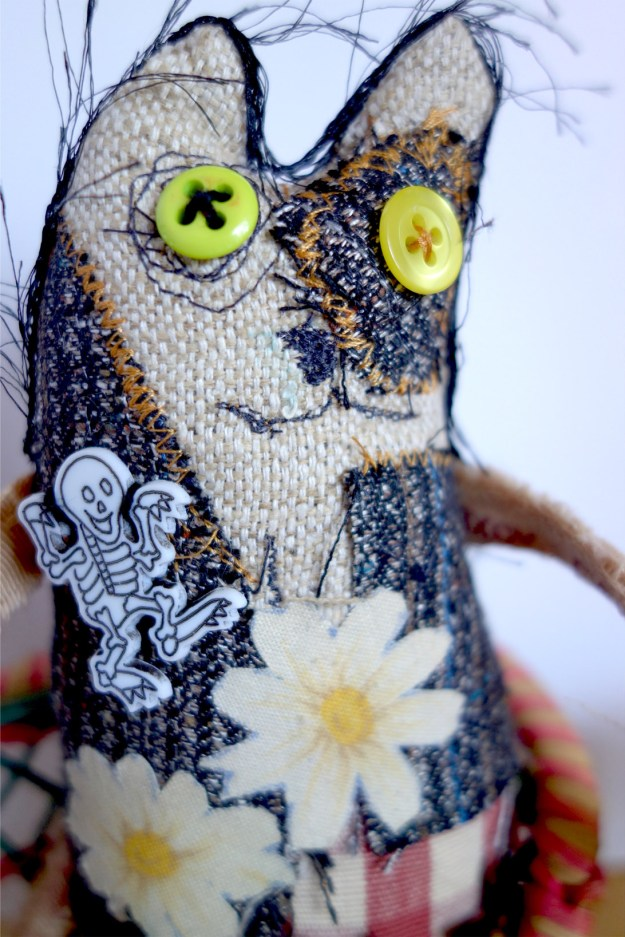 Closeup of Frankencat, a very cobbled together creature made from all kinds of scraps and such. Very punk looking cat doll.