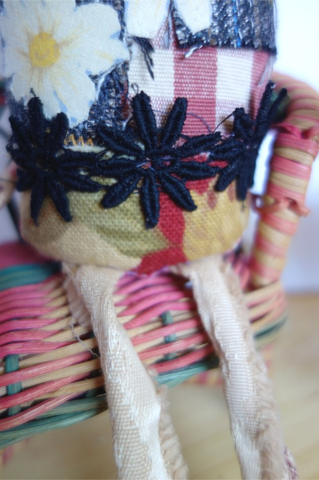 Closeup detail of black floral trim and scrawny legs of this funny little punk cat.
