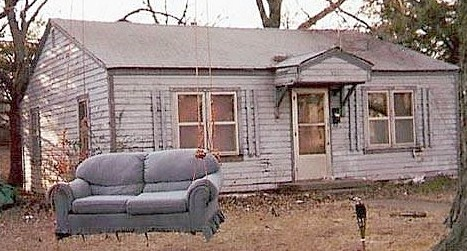 Photo of a tacky couch in a run-down front yard.