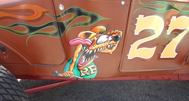 Hysterical cartoon drawing of Rat Frink emblazoned on the side of a hot rod. Rat fink has big teeth and bulging eyes.