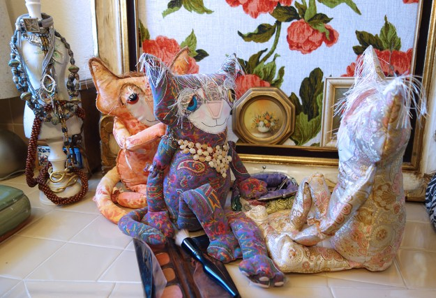 Three adorable soft sculpture cat dolls and are a bathroom counter with makeup and jewelry. Ginger is fastening a necklace around Eve's neck. Peach looks on.