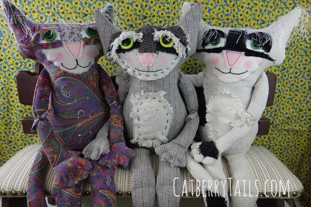 Rascal is seated with two other recently sewn cat dolls, one of whom is a female and is holding hands with him.