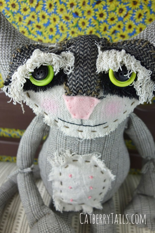 Up close photo of Rascal's face. His eyes are beautifully fringed with textured black, frayed wool and ivory yarn.