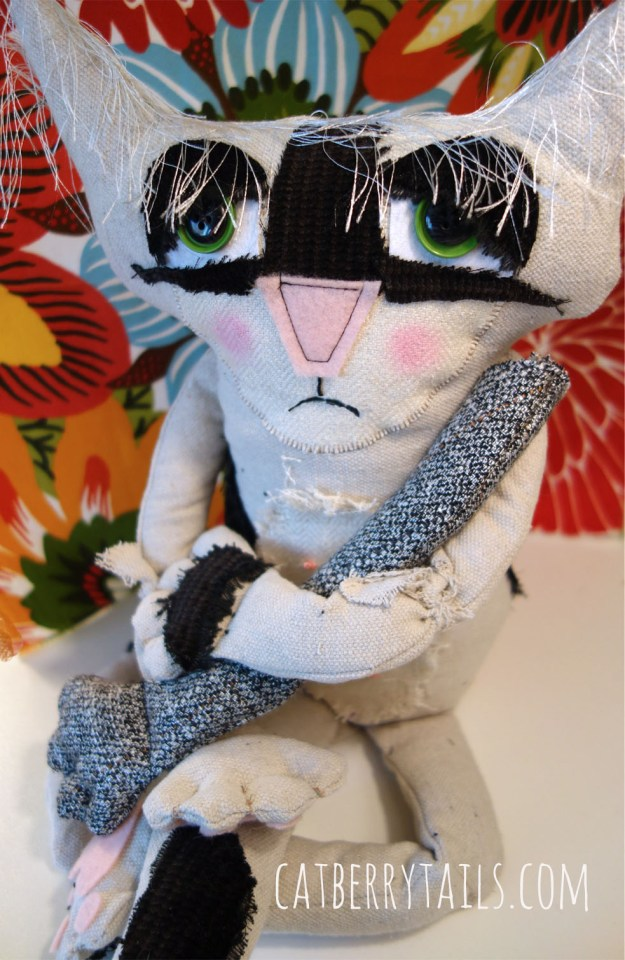 Bandit, the very cute soft sculptured cat doll, has a frown on his face as he is grasping a cat doll arm.