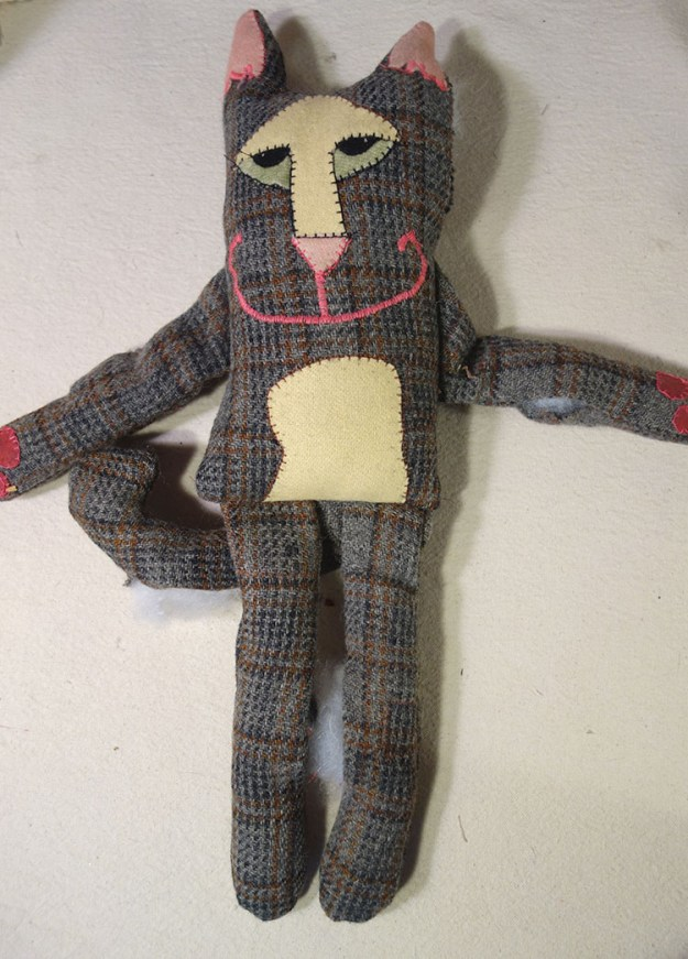 A partially finished cat doll made from a man's suit. It's a little stiff but the face is cute.