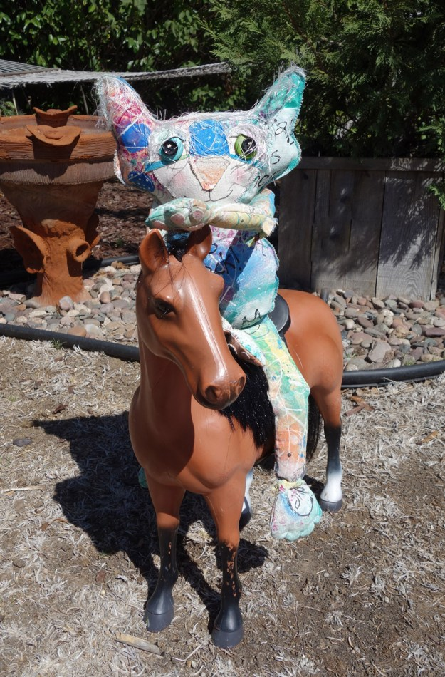 The Chairman, whimsical cat doll, sits on a large plastic toy horse in a sunny back yard.