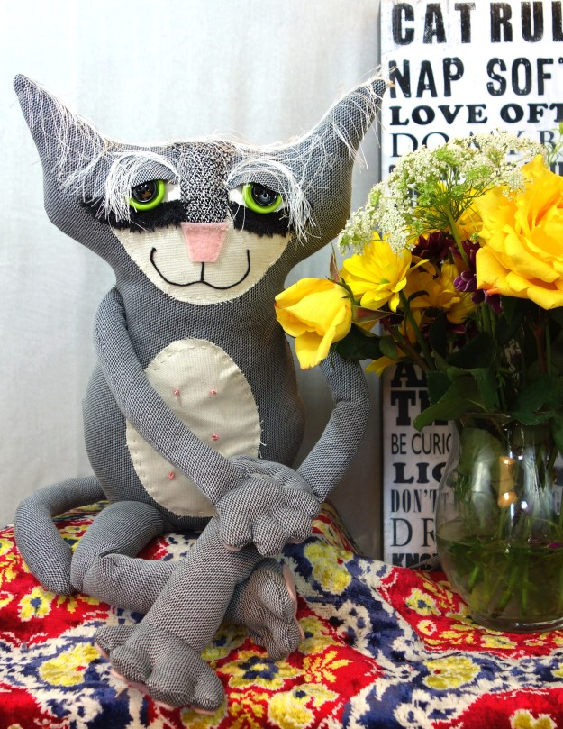 A soft sculpture cat made from upcycled clothing. He is grey and has an adorable ivory belly patch.