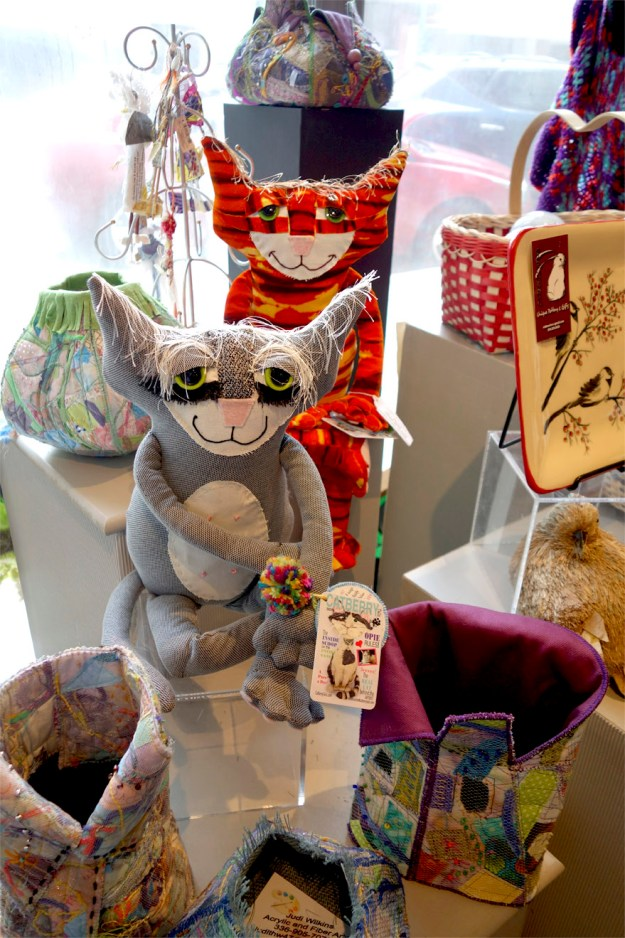 Two soft sculptured cats pose proudly in a gift shop of a gallery.