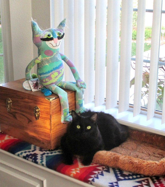 Soft sculpture cat sits with a real life black cat.