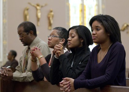 The Brooks family — Joe, Desiree, Gabrielle and Alyssa — pray after arriving for Sunday Mass at St. Joseph's Catholic Church in Alexandria, Va., in this 2011 file photo. (CNS photo/Nancy Phelan Wiechec)
