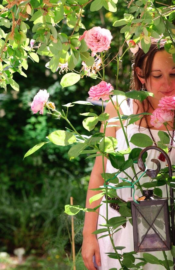Girl in garden smelling roses
