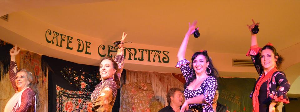 Primer plano de las cuatro bailaoras saludando al público con la mano alzada y al fondo se vislumbra el nombre del cafe de chinitas