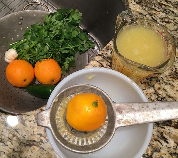 Juicing oranges and lemons to make Tequila Lime Chicken