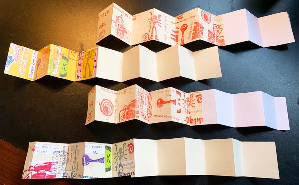 Old copies with color ink and red ink cut into two-inch strips, folded and glued to make mini accordion books.