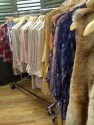 A rack of clothes featuring blouses, dresses, and the faux fur vest.
