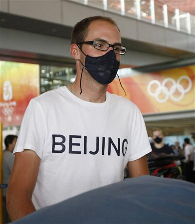 Bobby Lea, American Olympic cyclist, wears face mask when arriving in Beijing