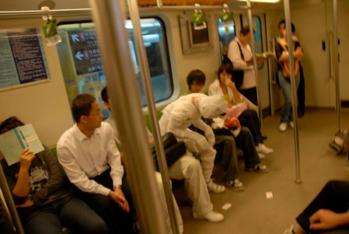 Shanghai metro mummy sits down with other passengers.