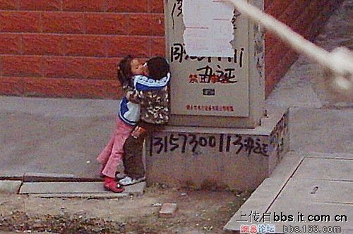 These two cute children are kissing.