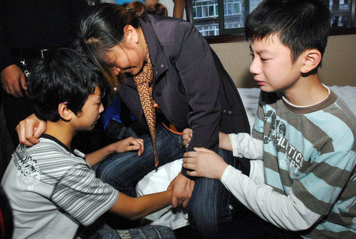 The rescued boy kneels before the university heroes' family members.