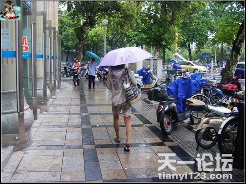 Ningbo, China - A Chinese beggar carrying a woman's bag and umbrella on the streets of Ningbo, China walks down the wet street