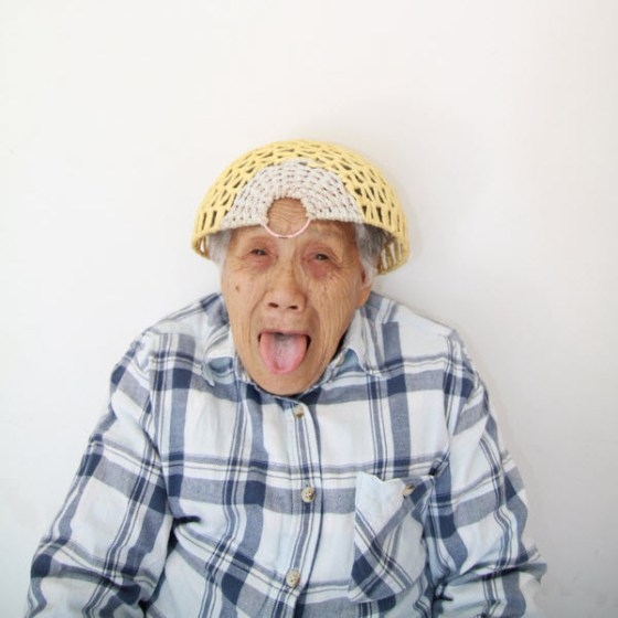Crazy Chinese granny wearing a basket on her head.