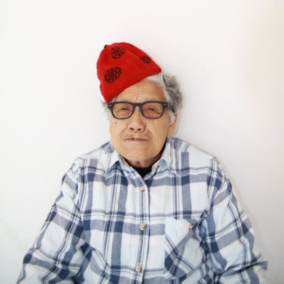 Crazy Chinese granny wearing a red beanie on her head.