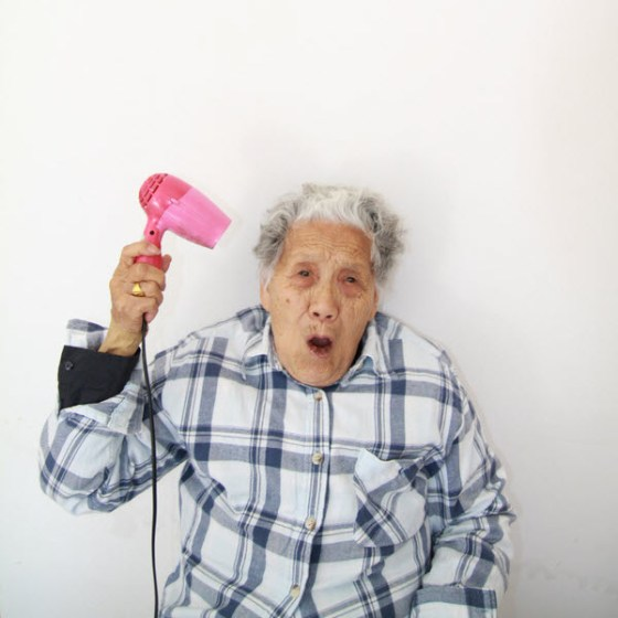 Crazy Chinese granny using a hair blowdryer.