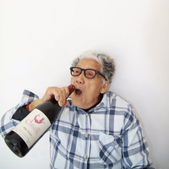 Crazy Chinese granny drinking from a large bottle of wine.