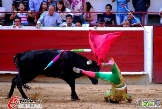 A Spanish matador flipped by charging bull.