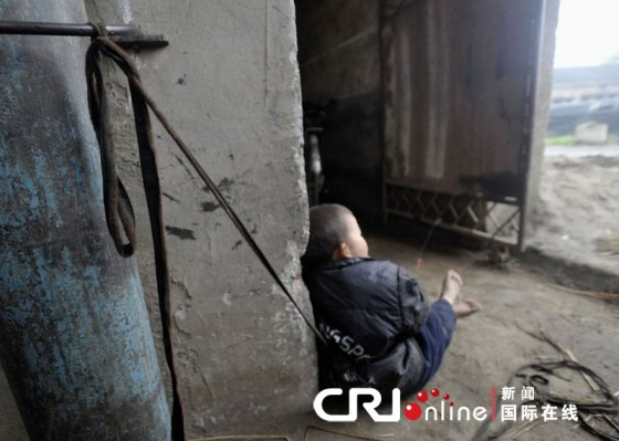 A little boy sitting on the ground of a brick factory workship in Zhejiang China.