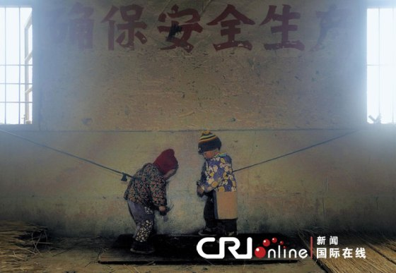 Two little Chinese children tied to windows in Zhejiang. Their parents tie them up so they do not run around and get into accidents.