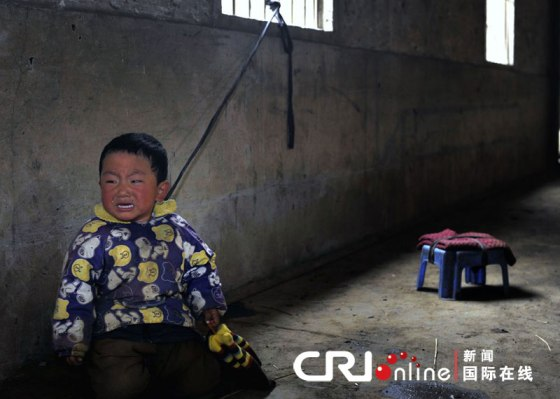 A little Chinese boy cries, a rope tying him like a leash to a window.