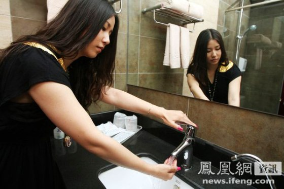 Zhang Yumo, a professional hotel tester tests the water coming out of a sink in a hotel.