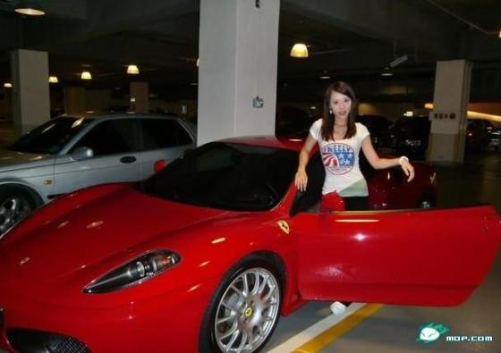 Chinese girl standing beside her red Ferrari.