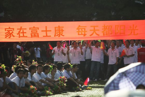 Foxconn workers at a rally holding up a banner that says their home is with Foxconn, that everyday is sunshine.