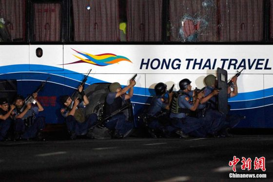 Police commandos take cover as the hostage taker fires at them while they assault a bus with tourists being held hostage at Quirino Grandstand in Manila August 23, 2010. Police were poised to storm a bus where a sacked former Filipino policeman was holding 15 Hong Kong tourists hostage in downtown Manila after shots were heard at the scene, TV pictures and a Reuters witness said. REUTERS/Erik de Castro