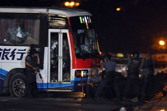 Philippine policemen take position as they start their attack on a tourist bus hijacked in Manila on August 23, 2010. An ex-policeman armed with a high-powered assault rifle hijacked a bus carrying more than 20 Hong Kong tourists including children in the Philippine capital on August 23, police said.   AFP PHOTO/TED ALJIBE