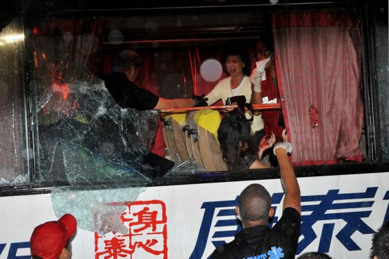 Paramedics help victims from the hijacked bus in Manila on August 23, 2010.  The gunman who seized a bus carrying Hong Kong tourists killed at least four of his hostages in the Philippines, doctors said.    AFP PHOTO / JAY DIRECTO