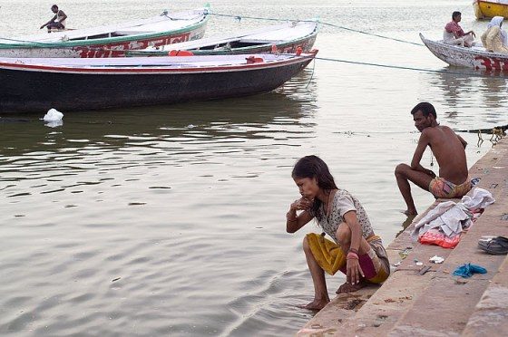 An Indian woman brushes her teeth with water from the Ganges River.