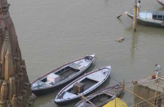 A floating corpse beside some boats in the Ganges River.