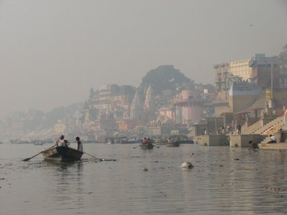 A row boat rows by a bloated corpse floats in India.