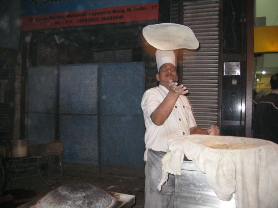 An Indian chef making bread.