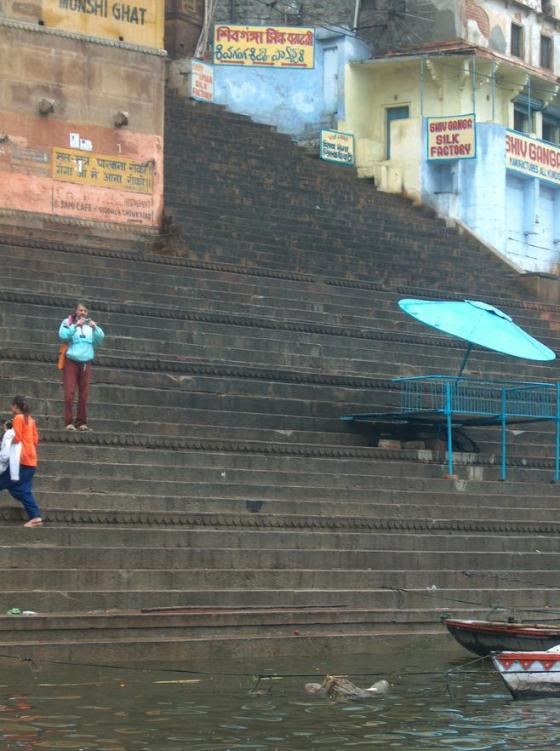 A dead body floats by the steps on the Ganges River.