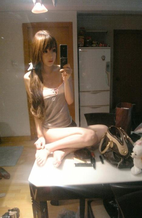 Wang Jiayun sitting on a table taking self-photos.