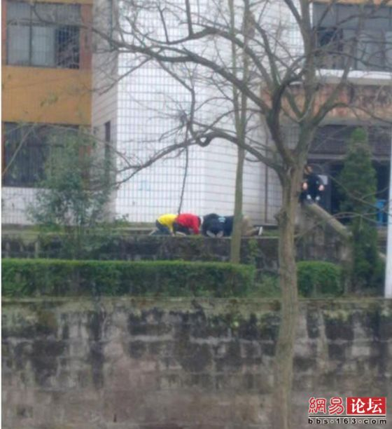 Chinese students kneeling on the ground writing self-criticisms while the teacher relaxes and smokes beside them.