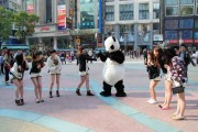 A panda and a group of girls wearing panda shorts along Shanghai's famous Nanjing Road.